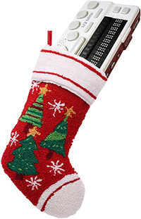 Photo of a red, quilted Christmas stocking adorned with Christmas trees and snow flakes hanging from a string with a BrailleSense U2 Mini 18 Cell Notetaker sticking out of the top of it.