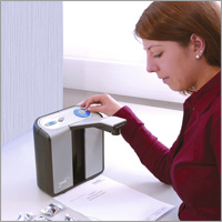 Photo of a woman using the Optelec ClearReader Plus.
