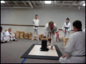 Photo of the LTrain at his TKD Black Belt Testing using his right fist to smash through a stack of wood on bricks in order to get to the Black Belt that had been placed underneath the boards.