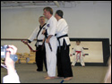 Photo of 6th Degree Master Rick Morad tying on the LTrain's Black Belt for the very first time.