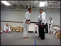 Photo of the LTrain bowing to 6th Degree Master Rick Morad after receiving his TKD Black Belt.